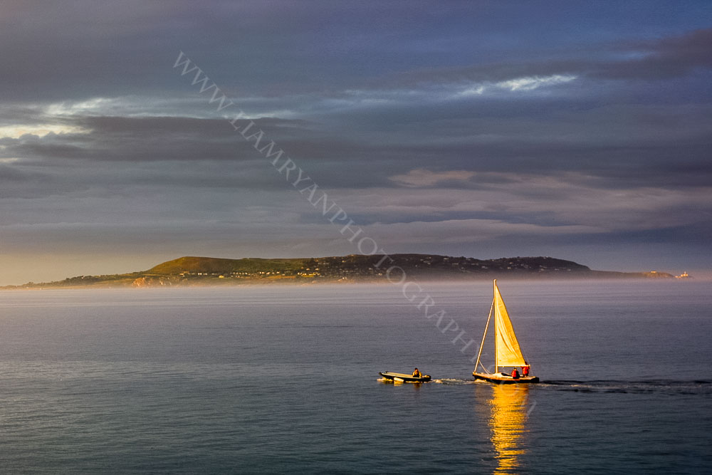 Sail Boat in golden August Sunset, with Howth and the Baily Lighthouse in the distance. Dún Laoghaire harbour  Dublin Ireland