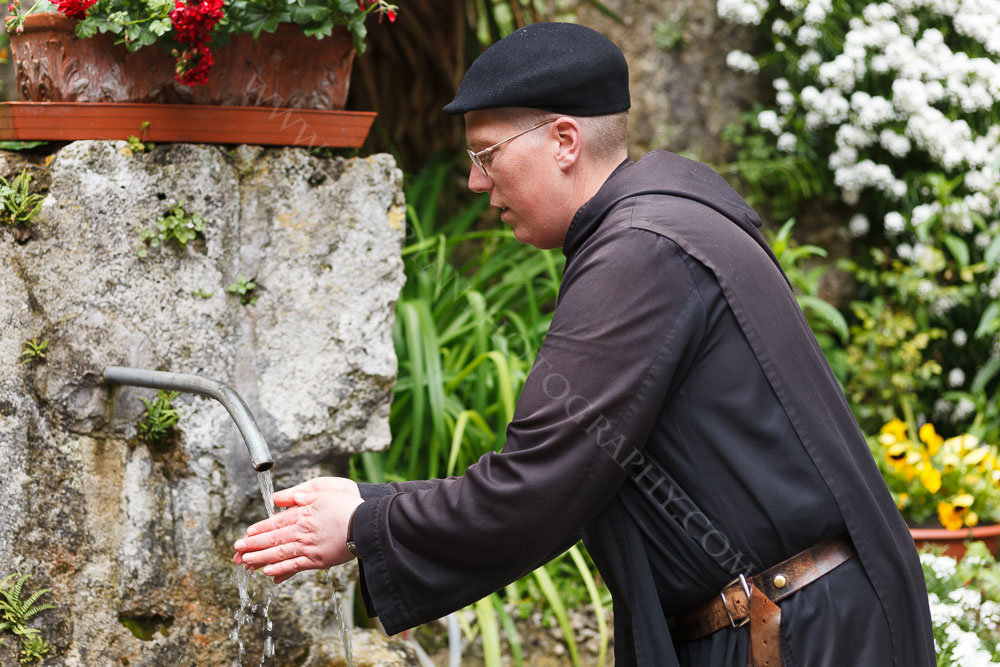 Padre Clementy washing his hands at St.Eutizio Abbey on his way to the chapel, Umbria, Italy.